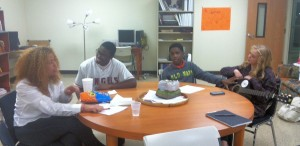 Four teens socialize before beginning rehearsal for Authoring Action, a downtown non-profit for teens interested in using the arts to effect change in the community.