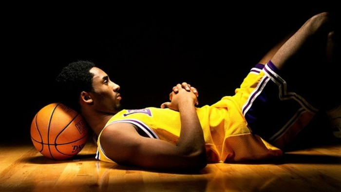 Kobe Bryant, sporting his old number 8, rests on a basketball and thinks to himself.